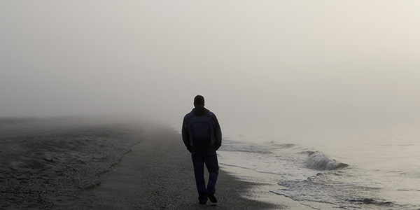 Lonely man walking on a beach